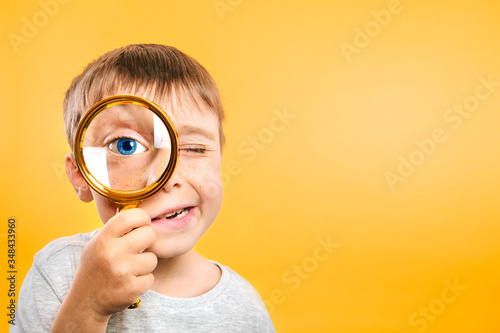 Child see through magnifying glass on the color yellow backgrounds Wallpaper Mural