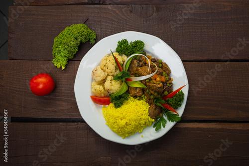 Fototapeta Zdrowy lunch lub obiad, serwowany na białym talerzu na ciemnym drewnianym stole. obraz