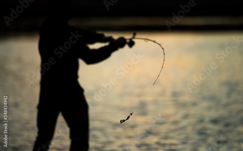 Photo Spinning angler throws the bait at sunset.