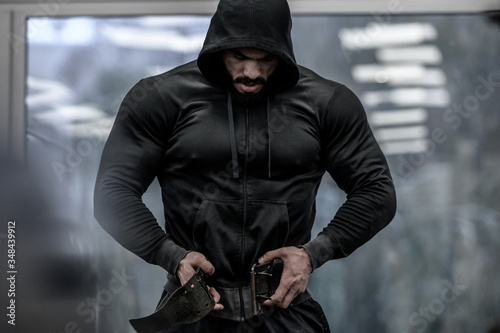 Fotografija strong young bearded mighty man in hoodie wearing powerlifting belt for heavy ha