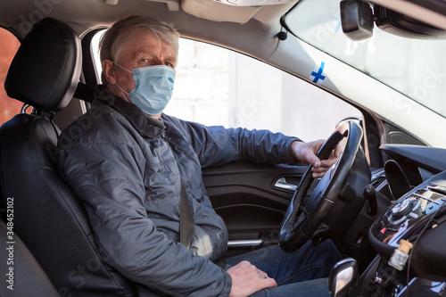 Fototapeta An elder Finn man sitting inside car wearing protective mask, prevention of viru