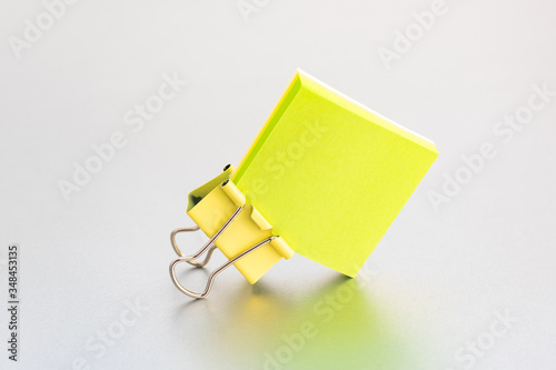 Obraz Yellow paper clip on clean color paper blok - a cover on a silver grey background - fototapety do salonu