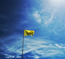 Low Angle View Of Yellow Flag Waving Against Blue Sky