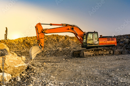 Fotomural Excavator moving stone and rock at a construction site