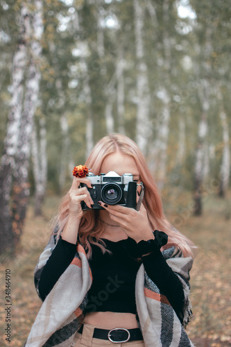 Photo CAUCASIC GIRL DOING PHOTOS WITH ANALOGIC CAMERA IN THE WOODS OF SIBERIA (RUSIA)