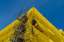 A Constuction-site With A Building In Scaffolding And Yellow Mesh.