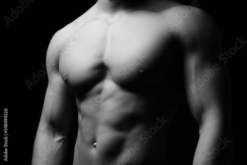 Muskulöser Männerkörper vor schwarzem Hintergrund