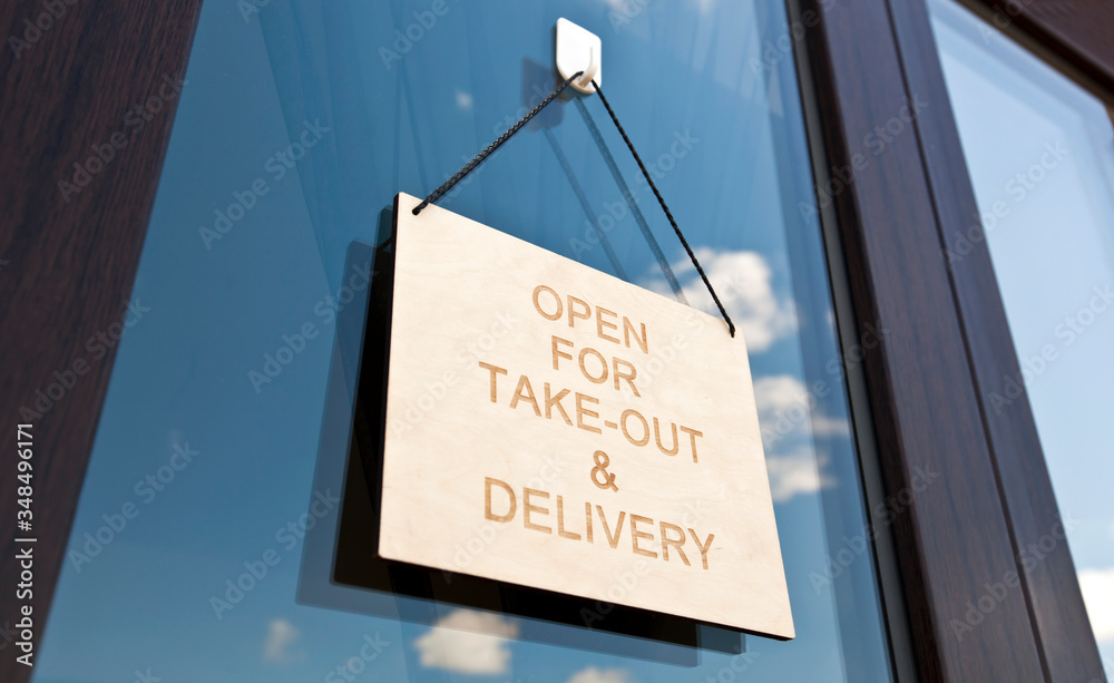 Fototapeta The wooden sign with text: Open for take-out and delivery hanging on the door in cafe