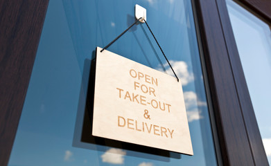The wooden sign with text: Open for take-out and delivery hanging on the door in cafe