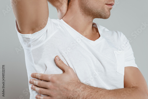 Cropped view of man showing sweaty armpit isolated on grey Wallpaper Mural