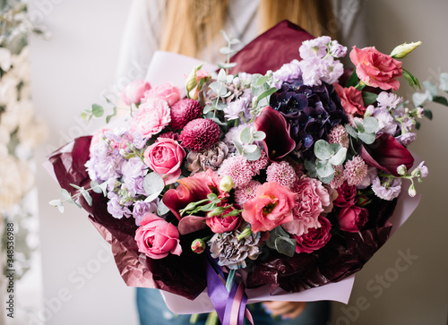 Very nice young woman holding big beautiful blossoming bouquet of fresh roses, hydrangea, carnations, matthiola flowers in purple and pink colors on the grey wall background © anastasianess