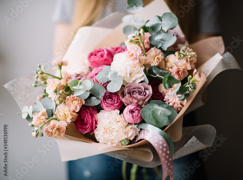 Very nice young woman holding big beautiful blossoming bouquet of fresh roses, carnations, matthiola, eucalyptus, flowers in pastel pink purple and cream colors on the grey wall background © anastasianess