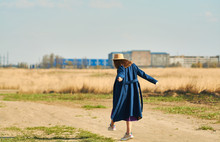 Happy Young Lady In Blue Coat With Beige Hat Runs In Field Early Spring.