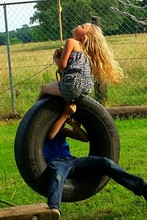 Siblings Playing On Tire Swing At Playground