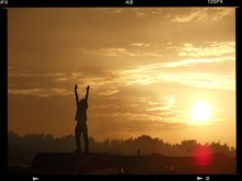 Silhouette Man With Arms Raised Standing On Houseboat Roof Against Sky At Sunset