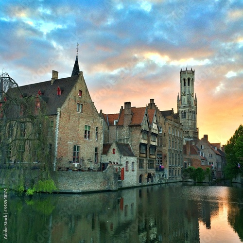 Canvas-taulu Belfry Of Bruges By Canal Against Cloudy Sky During Sunset