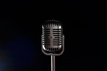 Silver Box-shaped Mic With Curved And Striped Ends With Poles With Black Background