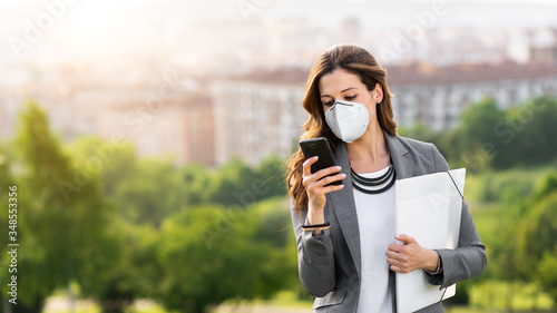 Fototapeta Young businesswoman wearing face mask outside during Covid-19 coronavirus health crisis. Professional woman using her smartphone. obraz