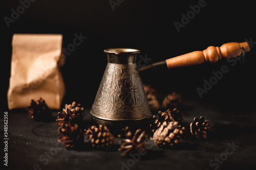 Fototapety, obrazy: Coffee Turk on a dark background, cones are scattered nearby. In the background is a bag with a coffee inside.