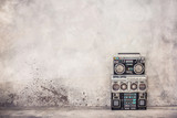 Retro old school design ghetto blaster boombox stereo radio cassette tape recorders from 80s front concrete wall background. Nostalgic Rap, Hip Hop, R&B music concept. Vintage style filtered photo
