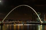 Illuminated Gateshead Millennium Bridge Over River At Night