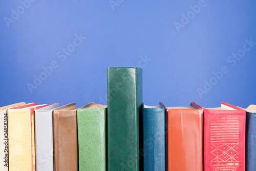 Fotografija Stack of old books, blue background, free copy space