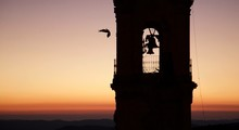 Low Angle View Of Bird Flying By Bell Tower Against Sky During Sunset
