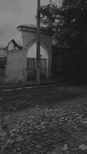 Arched Entrance With Closed Gate And Cobblestone Street