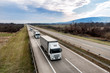 Convoy of Three White transportation trucks in line as a caravan or convoy on a country highway under a blue sky