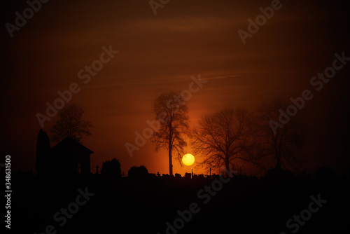 Fototapeta Krwawy wschód słońca nad starym cmentarzem obraz