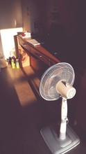 High Angle View Of Electric Fan On Floor With Sunlight