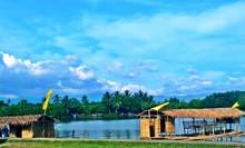 Stilt Houses By Lake Against Sky