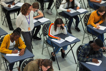 High School Teacher Supervising Students Taking Exam At Tables