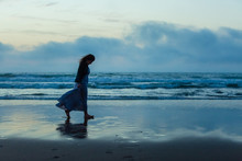 A Sad Woman With Long Hair In A Long Dress Is Walking At Sunset Along The Shore Of The Sea Or Ocean. Social Exclusion