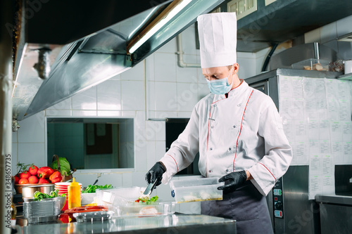 Fototapeta Food delivery in the restaurant. The chef prepares food in the restaurant and packs it in disposable dishes. obraz