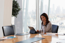Dedicated Businesswoman Using Digital Tablet In Conference Room