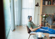 Man relaxing in living room, listening to music with mp3 player and headphones