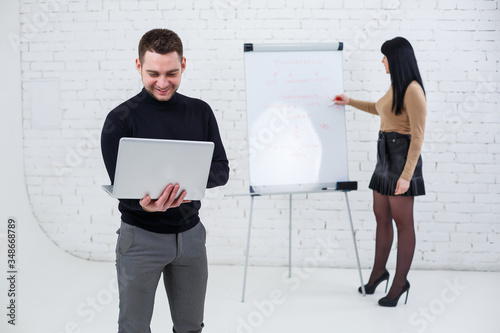 Manager businessman male announcer stands with a laptop while a woman writes a business promotion plan on a white board Canvas Print
