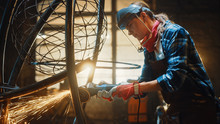 Close Up Of Young Female Fabricator In Safety Mask. She Is Grinding A Metal Tube Sculpture With An Angle Grinder In A Studio Workshop. Empowering Woman Makes Modern Abstract Metal Artwork.