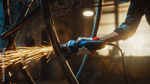 Fototapeta Close Up of Hands of a Metal Fabricator Wearing Safety Gloves and Grinding a Steel Tube Sculpture with an Angle Grinder in a Studio