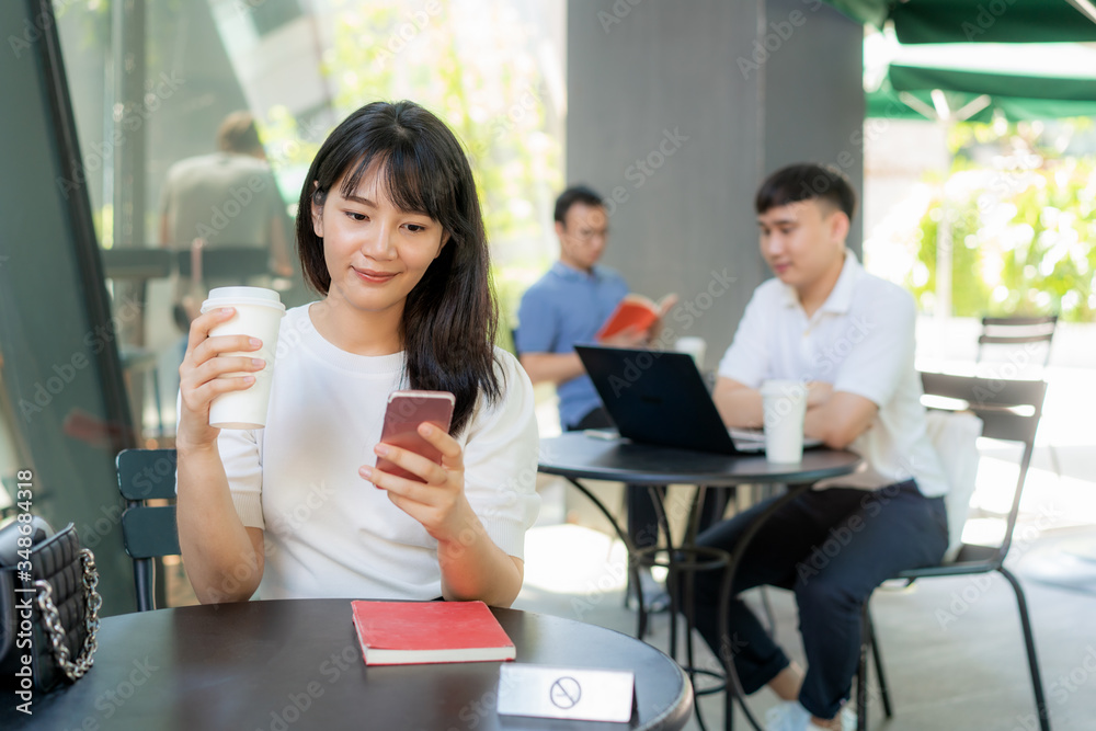 Fototapeta Asian young man and woman sitting one person per one table for distance of 6 feet distance protect from COVID-19 viruses for social distancing for infection risk at coffee cafe..