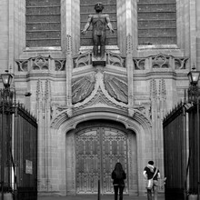Rear View Of Man And Woman Walking In Liverpool Cathedral With Large Male Sculpture