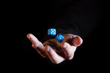Hand Throwing Dice Cubes In The Air Against Black Background