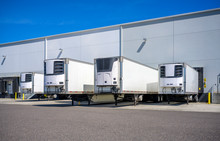 Refrigerator Semi Trailers Without Semi Trucks Standing At Warehouse Dock Gates Loading Frozen Cargo For Next Freight