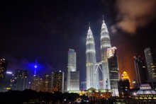 Low Angle View Of Illuminated Petronas Towers Amidst Buildings At Night