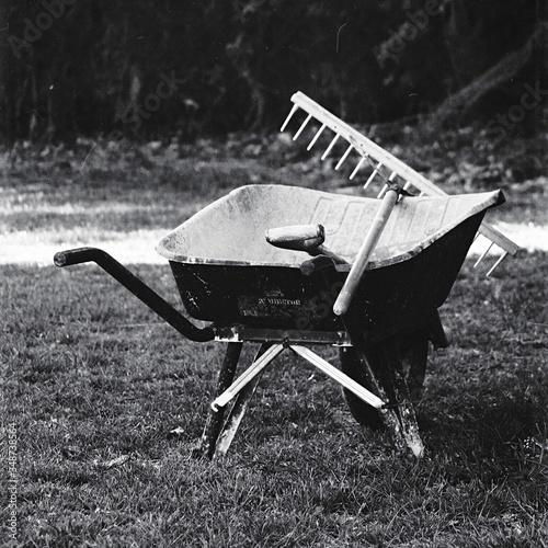 Billede på lærred Wheelbarrow With Gardening Fork On Field