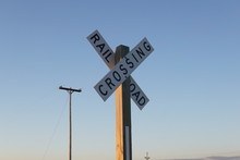 Railroad Crossing Sign Against Blue Sky During Sunset