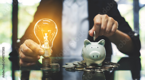 Cuadros en Lienzo A businesswoman putting coin into piggy bank and a light bulb over coins stack o