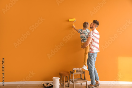 Little son helping his father to paint wall at home