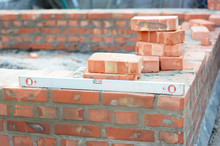 Building A Brick Foundation Wall Corner Of A House Construction Using Spirit Level To Keep The Brickwork Upright And Level On A Mortar Bed.